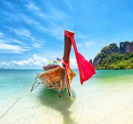 Tourism in Asia. Tropical island and tourist boat on exotic sandy beach - stock photo