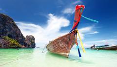 Adventure landscape background. Wooden fishing boat on sea coast of island Stock Photos