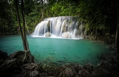 Clear water pond and silky waterfall in forest - stock photo