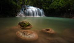 Wet stones in river stream in wild rainforest with scenic waterfall cascades  - stock photo