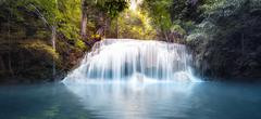 Cool fresh water pond in forest with smooth and silky waterfall cascades - stock photo