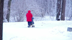 Woman with pram in winter Park - stock footage
