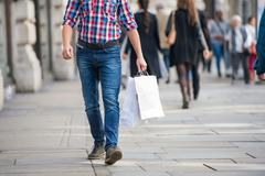 Unrecognizable man with shopping bags in the street, back view - stock photo