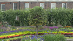 Kensington Gardens with brick building and flowers in London Stock Footage