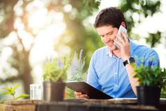 Gardener holding clipboard, making phone call, green sunny natur Stock Photos