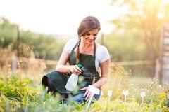 Young gardener in green apron sprinkling plants, garden - stock photo
