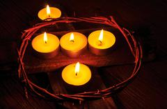 a crown of thorns and some lit candles on a wooden cross - stock photo