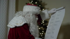Santa Claus checking his list on Christmas Eve Stock Footage