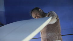 Man sanding new surfboard Stock Footage