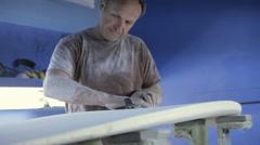 Man sanding new surfboard - stock footage