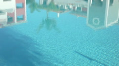 Reflections in swimming pool, camera pans to show woman by pool Stock Footage