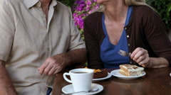 Happy mature couple, woman feeding cake to husband - stock footage