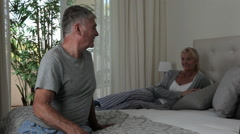 Mature couple relaxing on bed Stock Footage