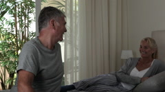 Mature couple relaxing in bedroom - stock footage