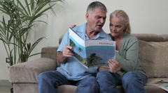 Mature couple looking at a holiday brochure Stock Footage