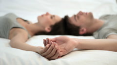Young couple lying on bed holding hands Stock Footage