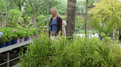 Couple choosing plants in garden centre Stock Footage