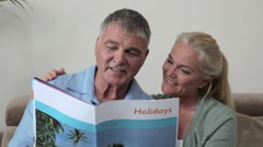 Mature couple looking at holiday brochure - stock footage
