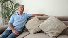 Senior man relaxing on sofa Stock Footage