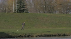 Man Sways With Fishing Rod Throws Bait Standing at Opposite Bank of a River on Stock Footage