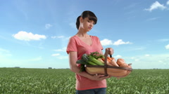 Stock Video Footage of Woman in field holding basket of homegrown vegetables
