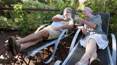 Couple sitting on garden chairs with wine Stock Footage