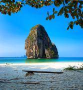Remote empty beach with rock formation in water. Traveling to Thailand - stock photo