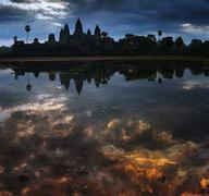 Dramatic sky and Angkor Wat silhouette reflect in lake after sunset Stock Photos