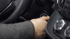 Hand putting car key to the keyhole, starting the car Stock Footage