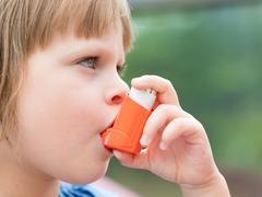 Portrait of a girl using asthma inhaler outdoors Stock Photos