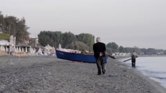 Old man who was walking on the beach going towards a boat pulled ashore Stock Footage