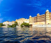 City buildings reflection on water of Pichola lake in India Udaipur Rajasthan - stock photo