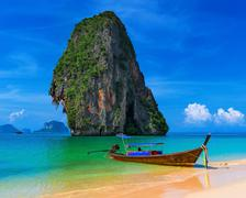 Wooden boat on exotic sandy beach with tropical sea at summer in Thailand Stock Photos
