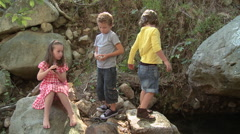 Girl sitting on rock and boys throwing stones - stock footage
