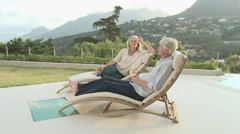 Mature couple relaxing on sunloungers Stock Footage