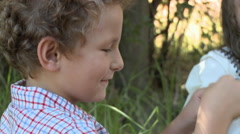 Boy putting flower on face and making girl laugh Stock Footage