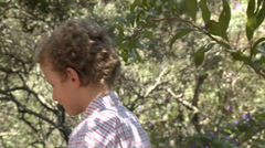 Boy walking along log by river Stock Footage