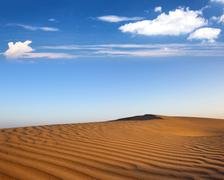 Beautiful evening landscape of desert with brown rippled sand and blue sky wi Stock Photos