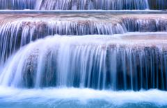 Clean blue water flows on cascades of waterfall - stock photo