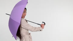 Young woman with umbrella in wind - stock footage