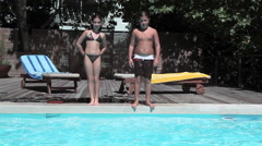 Boy and girl jumping into swimming pool Stock Footage