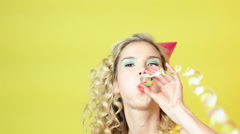 Young woman in party hat blowing streamer Stock Footage