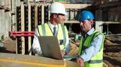 Mature men using laptop on construction site Stock Footage