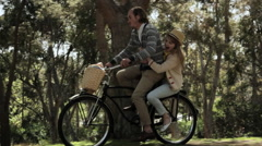 Couple riding one bicycle through forest Stock Footage