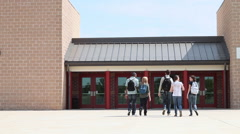 High school students walking into school, one student running behind Stock Footage