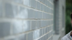 Young woman leaning on wall and smiling at camera Stock Footage