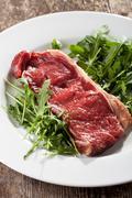 Raw loin steak on rocket salad Stock Photos