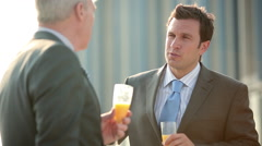 Businessmen talking and toasting with bucks fizz Stock Footage