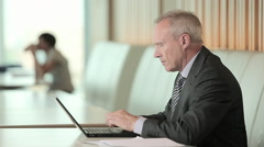 Businessman using laptop and looking at camera - stock footage