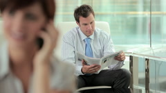 Woman on cellphone and businessmen talking Stock Footage